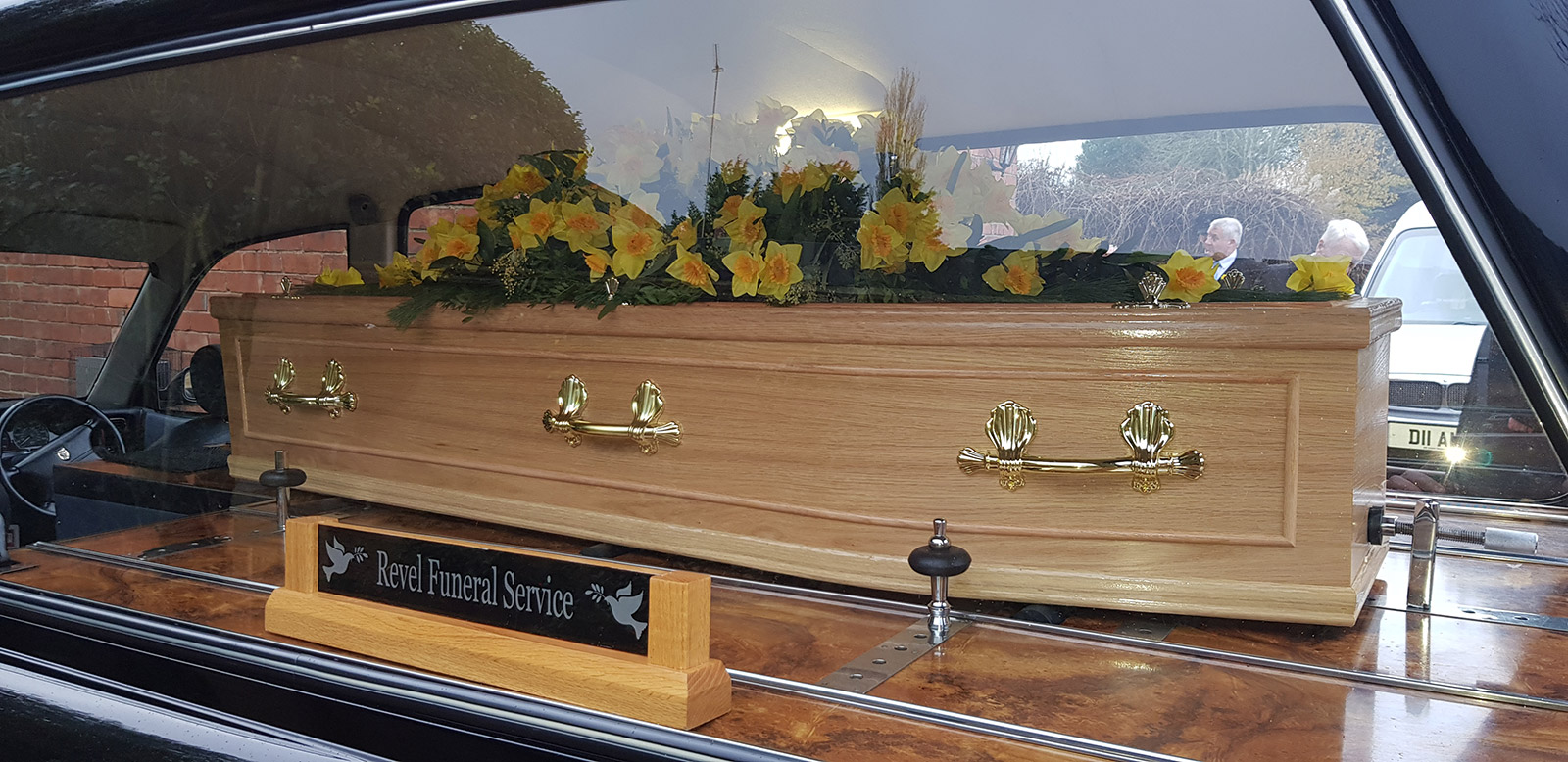 Coffin in Hearse with Flowers